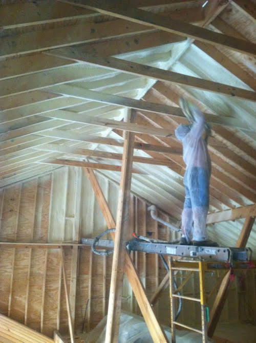 Technician applying spray foam to ceiling